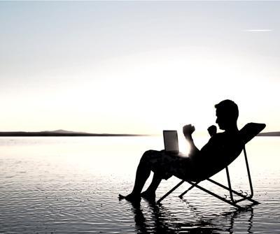 Mężczyzna wypoczywający nad morzem, preferując zarabianie pieniędzy poprzez dochód pasywny