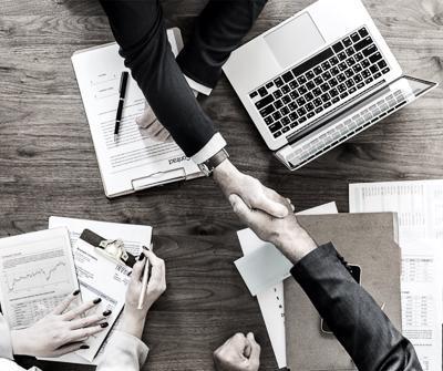 Spotkanie, podczas którego doradca finansowy podaje rękę kredytobiorcy