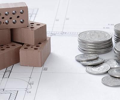 Cegły, monety oraz wyliczenia wskazujące jak korzystnie kupić mieszkanie na rynku pierwotnym