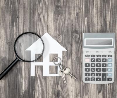 Lupa, makieta nieruchomości i klucze do domu, wskazujące na to, jak wybrać najlepszy kredyt hipotezny