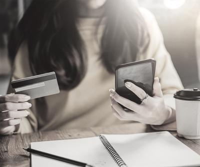 Młoda dziewczyna z kartą kredytową w dłoni, szukająca na smartfonie porad, jak uzyskać kredyt hipoteczny dla Ukraińca