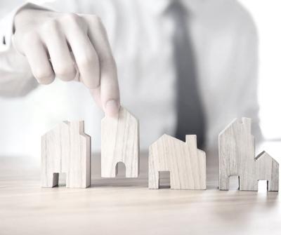 Mężczyzna układający obok siebie makiety domów, co symbolizuje porównanie kredytów hipotecznych