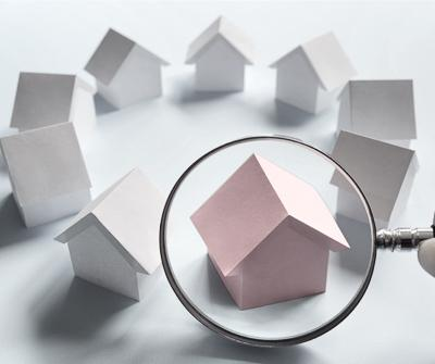 Grafika ukazująca lupę skierowaną na makiety domów, symbolizując narzędzie, jakim jest porównywarka kredytów hipotecznych