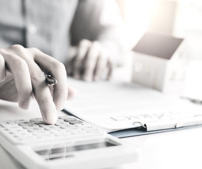 Doradca liczący na kalkulatorze wartość opłaty, jaką stanowi prowizja za udzielenie kredytu