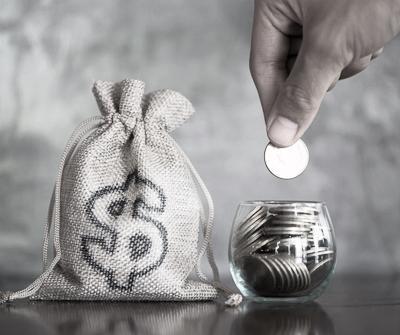 Worek z pieniędzmi i monety w szklanym naczyniu wskazujące na raty malejące