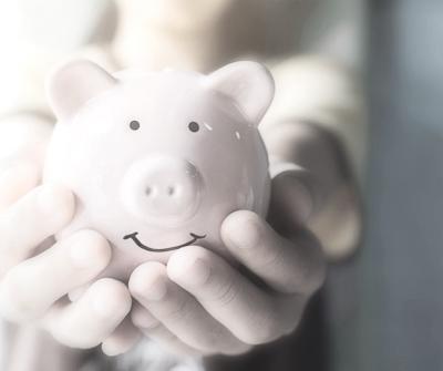Osoba trzymająca w dłoni skarbonkę, symbolizującą raty równe dla spłacanego kredytu