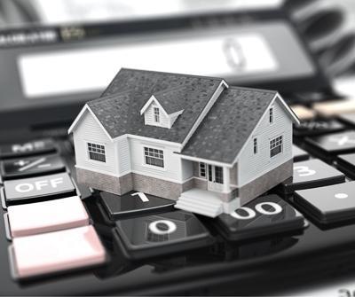 Miniatura nieruchomości ułożona bezpośrednio na kalkulatorze, wskazując na ubezpieczenie kredytu hipotecznego