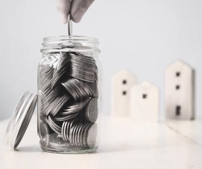 Pieniądze gromadzone w słoiku, wskazujące na wartość, jaki powinien stanowić zadatek przy zakupie nieruchomości